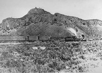 "The train pictured is the Jupiter which carried Leland Stanford, one of the ""big four"" owners of the Central Pacific, and other railway officials to the Golden Spike Ceremony. Notice the Native Americans on the hill overlooking the train."