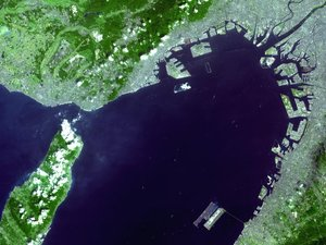 Satellite photo of Kansai Airport (lower-right island) in Osaka Bay.  is being built on the unfinished island near the middle of the photo. Central Osaka is in the upper-right corner.