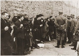 Captured inhabitants of the Ghetto await removal to the  for deportation.
