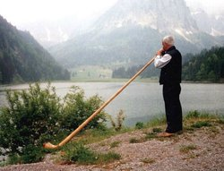 A Swiss playing an alphorn near a lake