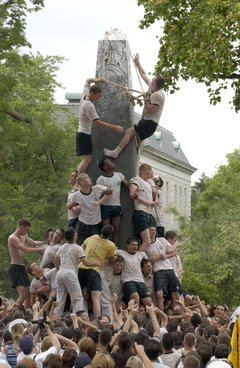 Teamwork: Fourth Class Midshipmen lock arms and use ropes made from uniform items as they brace themselves climbing the Herndon Monument
