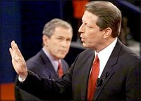 Al Gore makes a point during a  during the 2000 election as George W. Bush looks on.