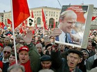 "A demonstrator carries a portrait of Gennady Zyuganov in a 2003 demonstration against the Putin government. The placard says ""Zyuganov: With Russia, Motherland, and the People."""