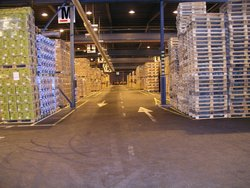 Inside Green Logistics Co., Kotka, Finland. The image shows goods loaded on pallets to the left of the aisle, and stacked pallets with no loads to the right of the aisle.