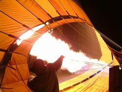 A hot air balloon is prepared for flight by inflation of the envelope with propane burners